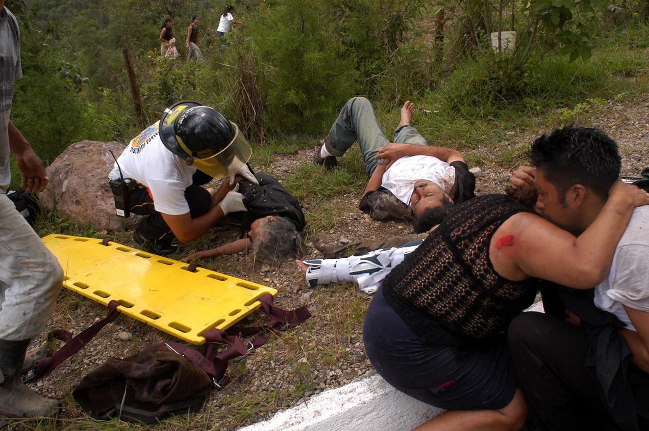 Pasajeros lloran y son atendidos por bomberos luego de que el autobús en el que viajan cayera en un barranco.