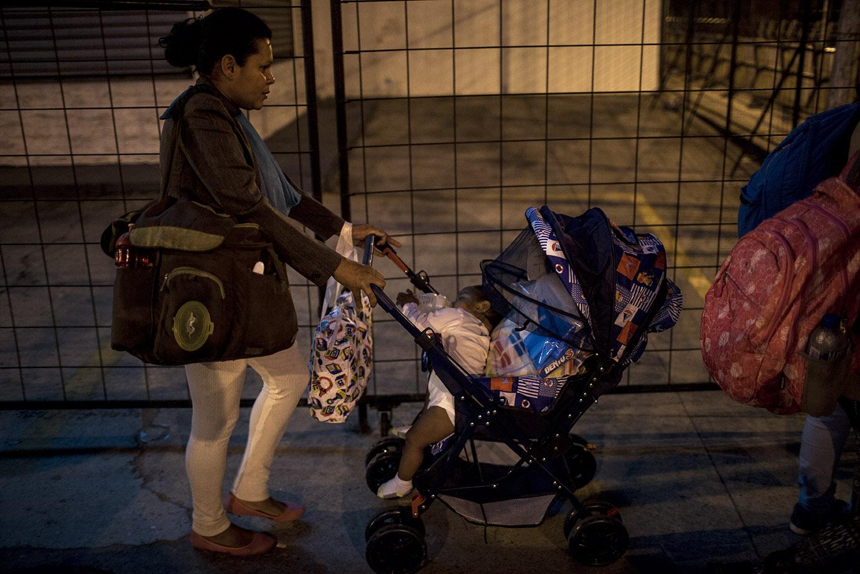 Una madre lleva la hija de pocos meses en el carruaje, acomodada entre paquetes y ropa