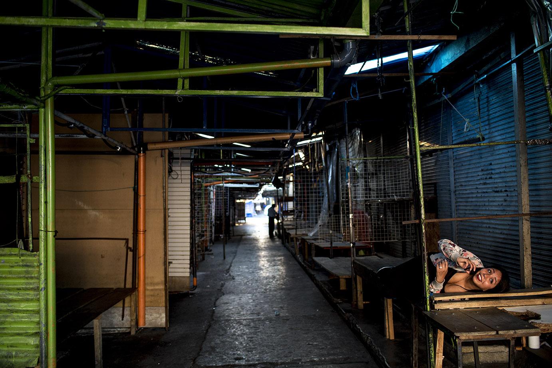 Alexandra López, 27, toma un descanso al finalizar la tarde del jueves 19, en el mercado de la 18 calle, zona 1, desolado, donde sólo ella y pocos mas se mantienen, ahora, vendiendo mascarillas y gel antibacterial. Simone Dalmasso