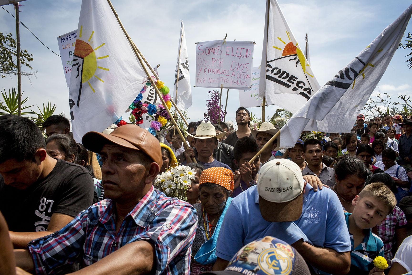 Varias banderas de Codeca alzadas durante el recorrido fúnebre hacia el cementerio de la comunidad.