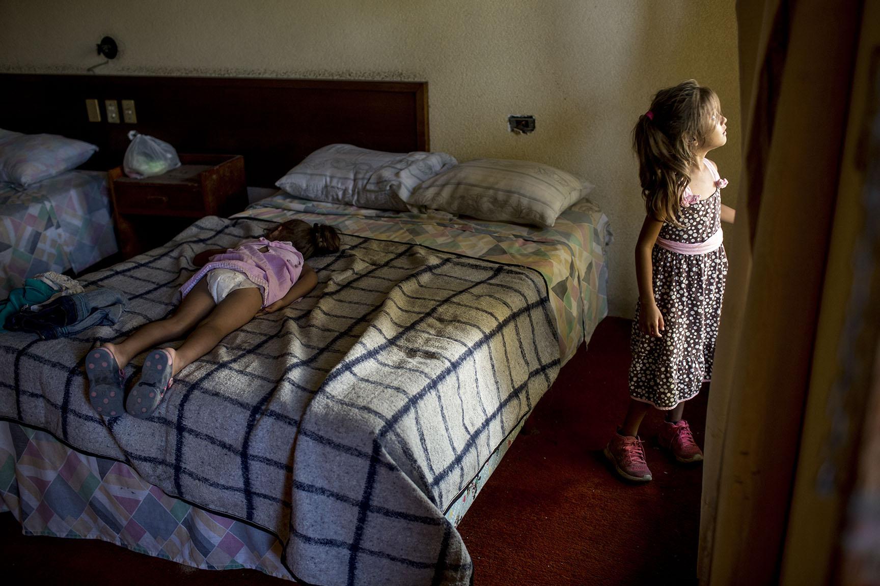 Astrid Melara, 6, mira desde la ventana de un cuarto del hotel, donde pasará la noche con su hermana Nicole, 5, ya dormida encima de la cama / Simone Dalmasso