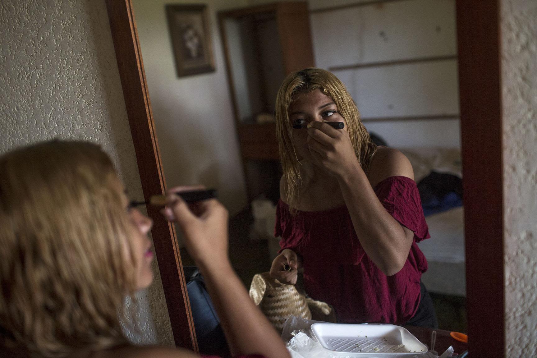 Kensy Gómez, 18, originaria de San Pedro Sula, se maquilla frente al espejo de su cuarto, antes de emprender nuevamente el viaje / Simone Dalmasso