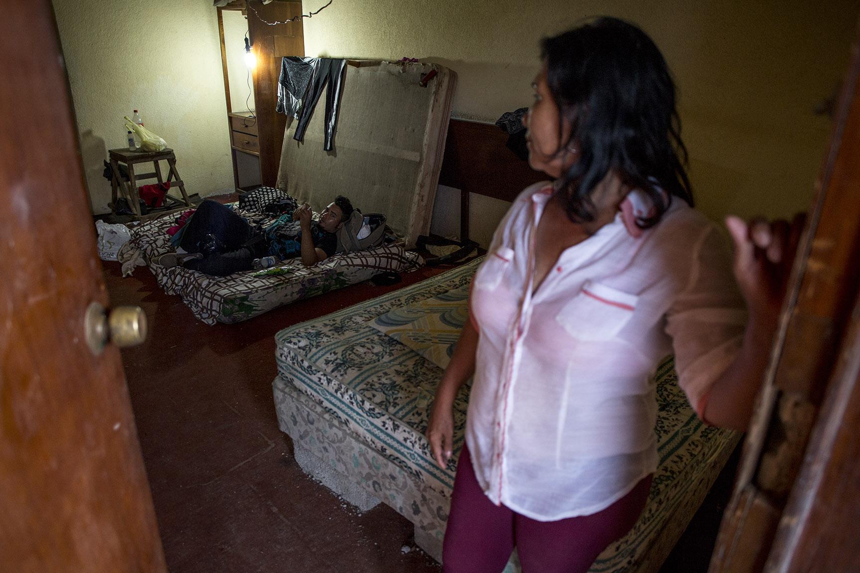Jairo Savillón, 23, descansa en la cama de un cuarto, custodiado por su madre, Ana María, 55. El joven anda muy trastornado por las condiciones duras del viaje / Simone Dalmasso