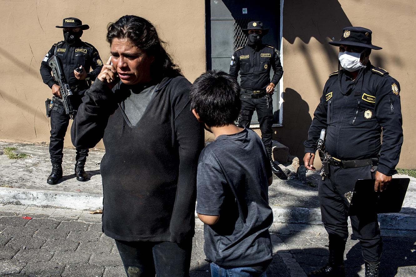 El jueves 26, un niño con su madre mira a los policías que lo rodean, frente al albergue de la zona 8 donde llegaron para refugiarse en compañía de otras dos menores y dos adultos más. La señora, viuda, cuya familia había sido desalojada ese día, estaba desesperada por otra hija que, supuestamente, andaba vagando en la calle amenazada de muerte. Simone Dalmasso