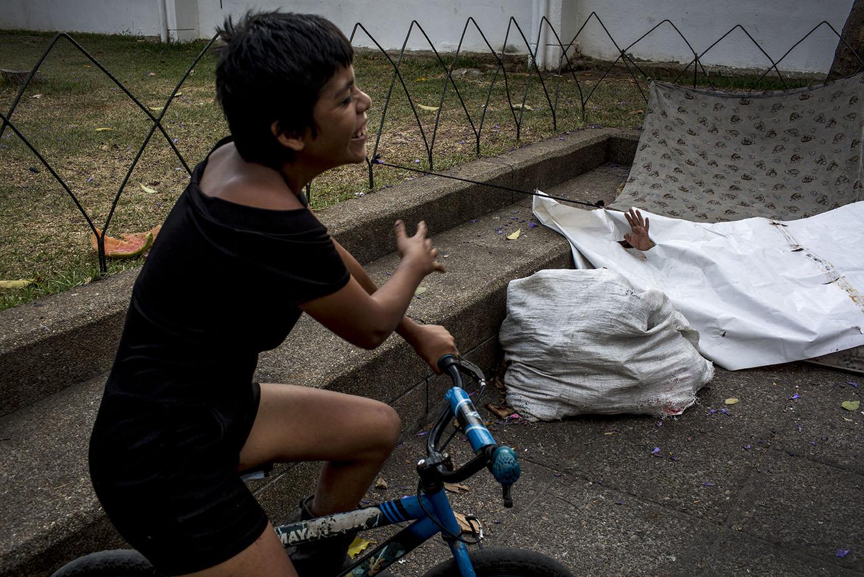 Benjamín, 28, originario de Gracias a Dios, departamento de Lempiras, Honduras, saca una mano de la lona en la que suele pasar la noche, en el parque central de la ciudad, provocando las risas de Janilet. Simone Dalmasso