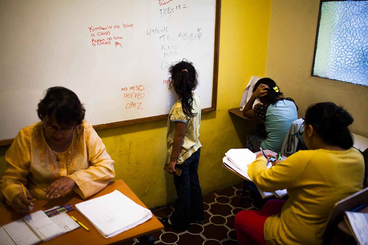 Una niña de seis años practica caligrafía en el pizarrón de la escuela del hogar, mientras sus compañeras estudian.