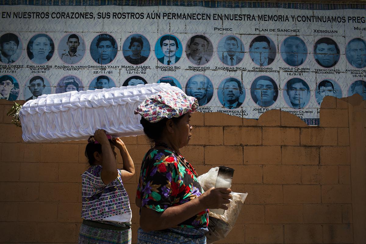 El día siguiente, el cortejo fúnebre rodea las paredes del cementerio de Rabinal adornado con los rostros de los desaparecidos en los años Ochenta