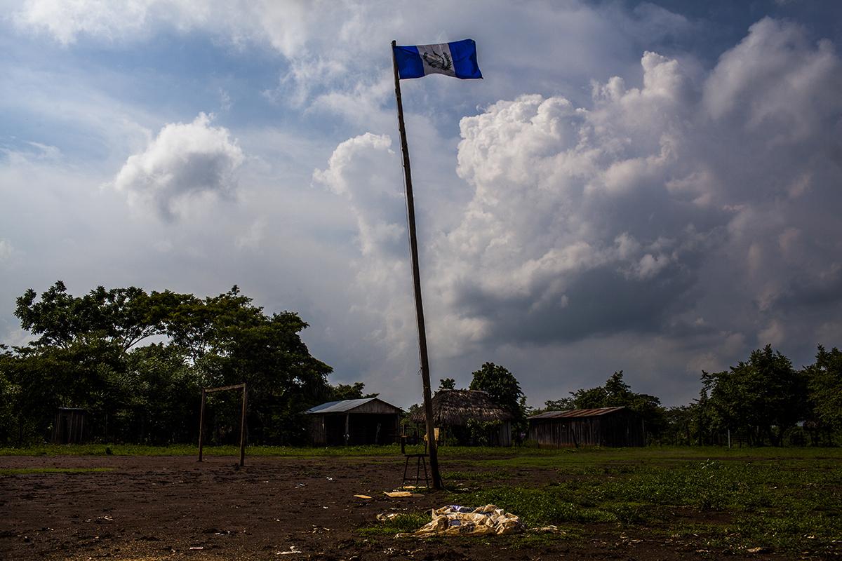 En el medio del campo de fútbol, al lado de la escuela, la bandera nacional flamea al viento quemador de las primeras horas de la tarde.