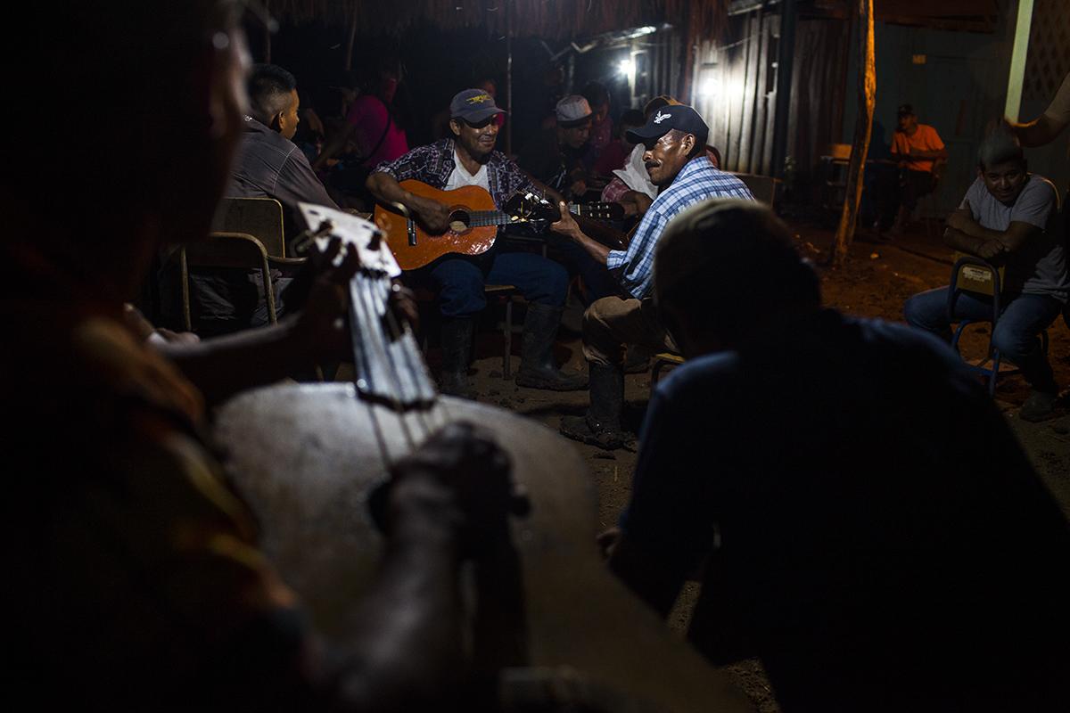 Los músicos suben el ánimo de la comunidad durante la noche de vigilia.