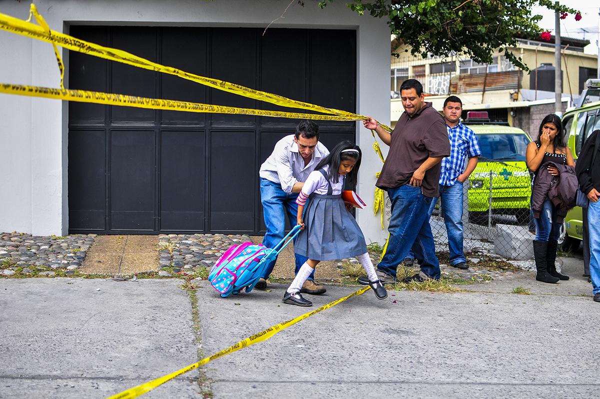 Un padre le abre el paso a su hija, en medio de una escena del crimen