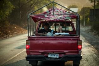 Dos jóvenes viajan en la trasera de un pick up a la altura de Guastatoya, El Progreso.