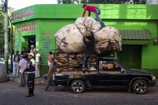 Algo sorprende mientras unos hombres cargan chatarra en Chiquimula.