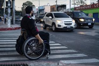 Un hombre en silla de ruedas espera su oportunidad de cruzar una calle en la Ciudad de Guatemala.