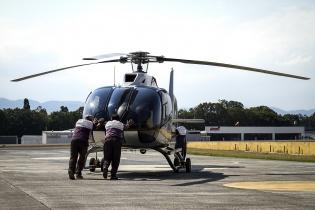 Empleados del aeropuerto La Aurora, en ciudad de Guatemala, ponen a punto un helicóptero antes de su despegue.