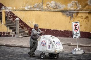 Un viejo vendedor ambulante de helados descansa frente al estadio Mario Camposeco, en Quetzaltenango.