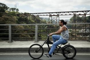 Un hombre cruza el Puente Belice en ciclomotor, en ciudad de Guatemala.