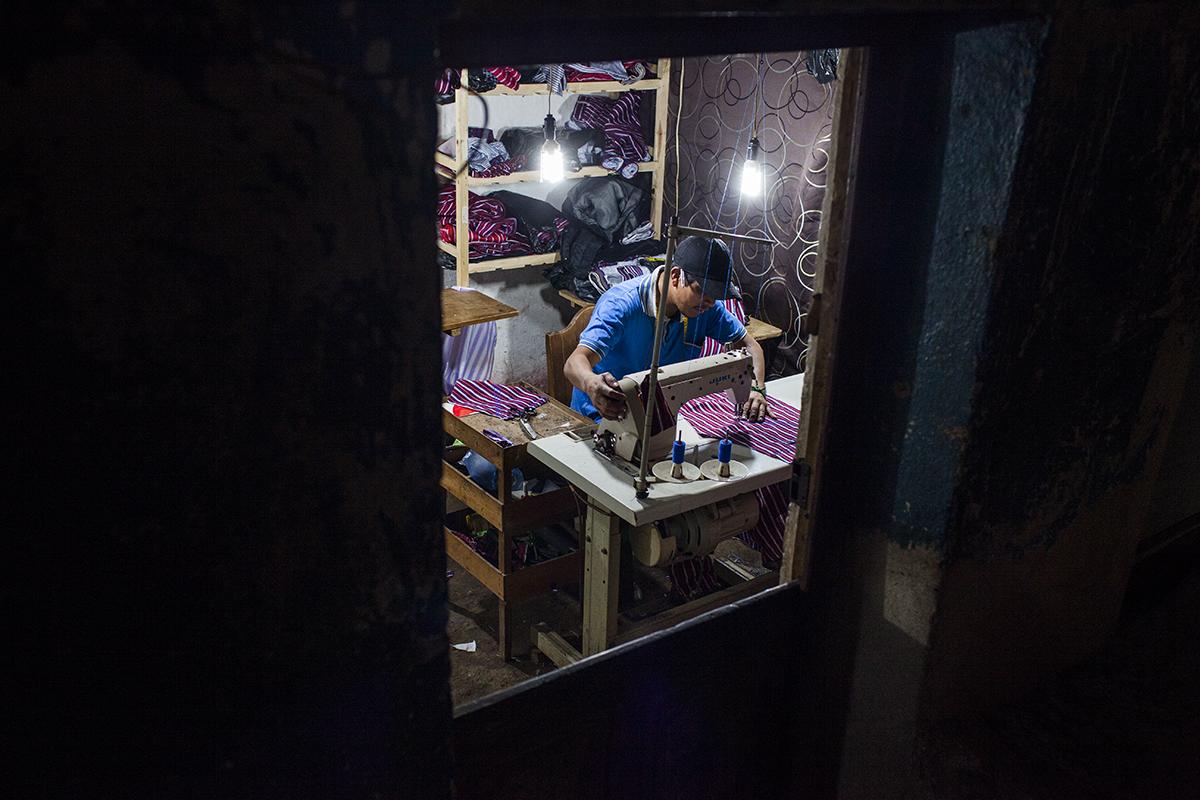 La noche del 31 de octubre, un sastre sigue trabajando para terminar los pedidos que tendrán que estar listos para el día siguiente.