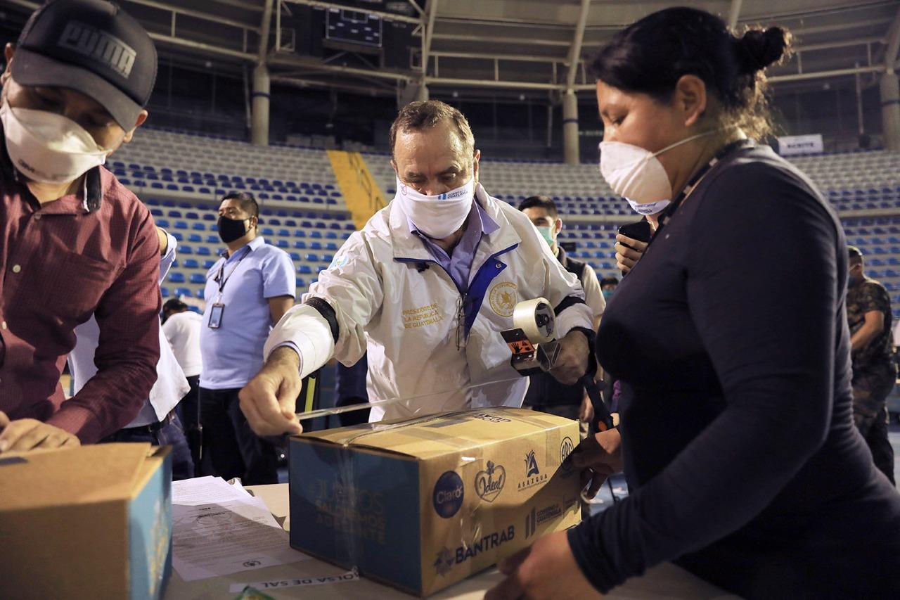 El presidente de la República, Alejandro Giammattei ayuda a empacar cajas de alimentos que distribuirán a la población más afectada por la crisis económica del COVID19