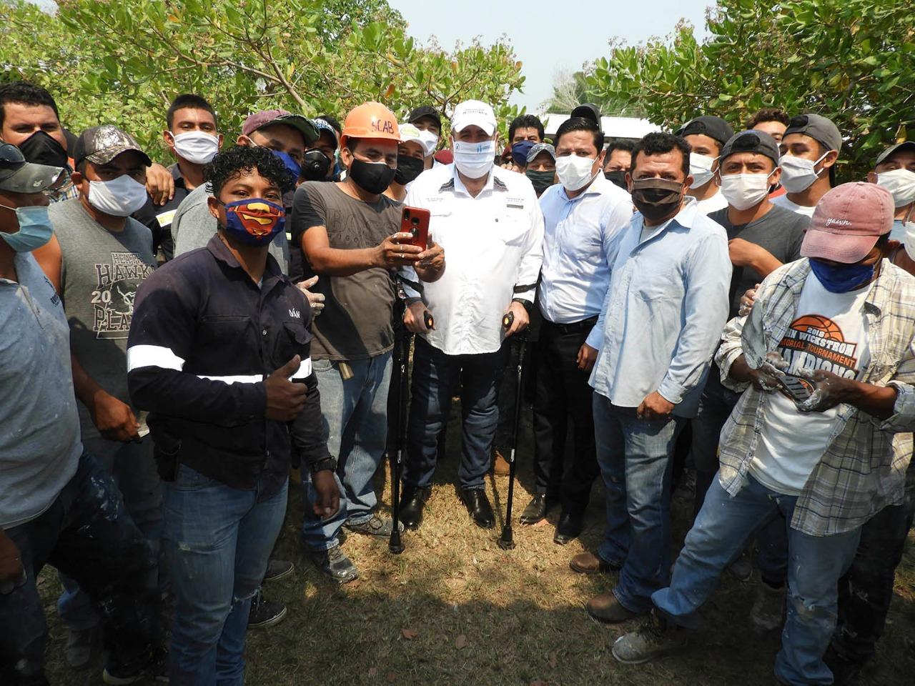 Alejandro Giammattei en una foto junto con el personal de gobierno y trabajadores locales en el área donde construirán el hospital temporal de Petén, el 14 de abril.